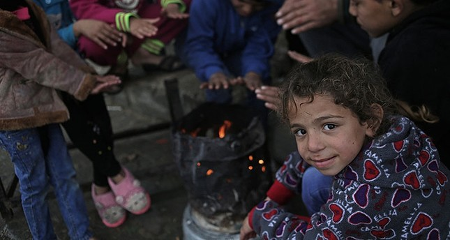 Palestinian children's warm themselves by fire outside their house in the street of Beit Hanun town northern Gaza Strip, during stormy weather in Gaza Strip, Jan. 27, 2018. (EPA Photo)
