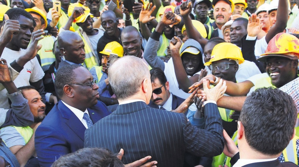 President Erdou011fan (C) shake hands with Senegalese workers as Senegal's President Macky Sall looks on, Dakar, March 1.