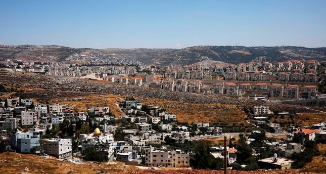A view of Palestinian houses in the village of Wadi Fukin with the Israeli settlement of Beitar Illit in the background, the occupied West Bank, June 19, 2019. REUTERS