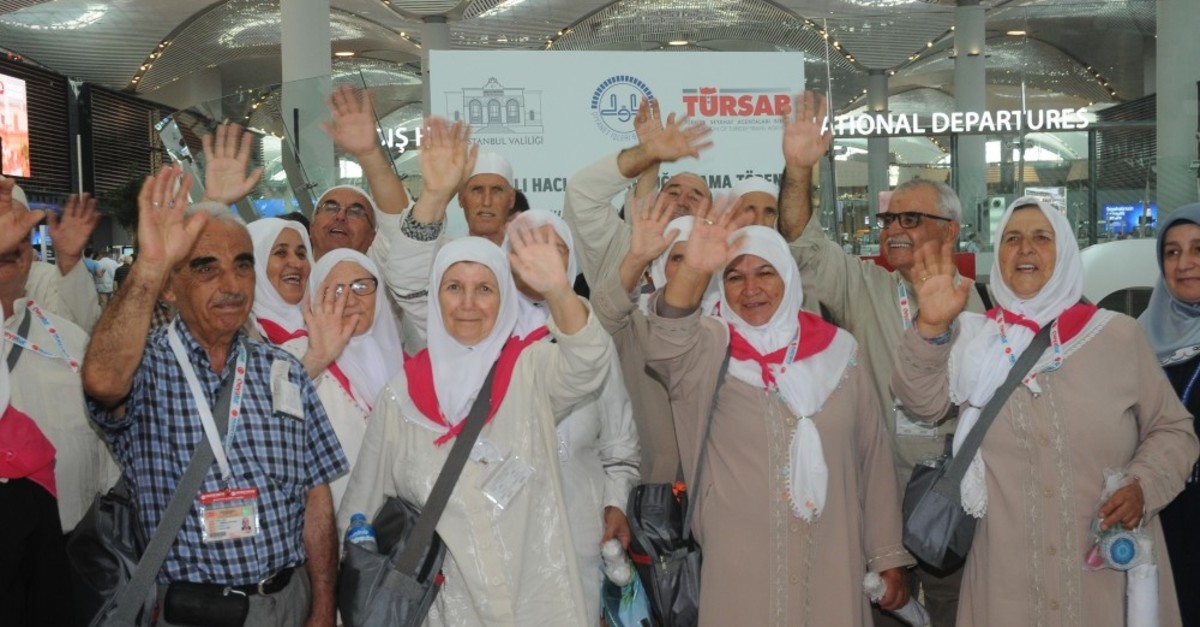 Pilgrims wave before they board an airplane to Saudi Arabia, July 5, 2019.