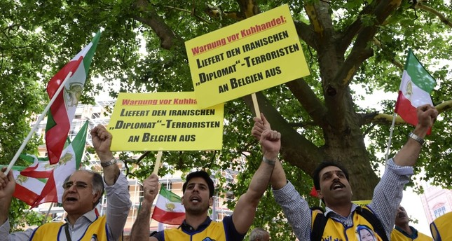 Activists hold placards reading 'Deliver the Iranian diplomat - terrorist to Belgium' during a demo calling for the extradition of a secret service officer to Belgium in front of the Federal Foreign Office in Berlin on July 11, 2018. (AFP Photo)