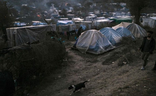A dog runs past tents at the makeshift camp next to the Moria refugee camp on the Greek island of Lesbos, Jan. 22, 2020. AFP