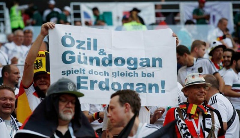 German supporters at a game in the World Cup 2018 hold a sign saying u201cu00d6zil, Gu00fcndou011fan go and play for Erdou011fan.u201d