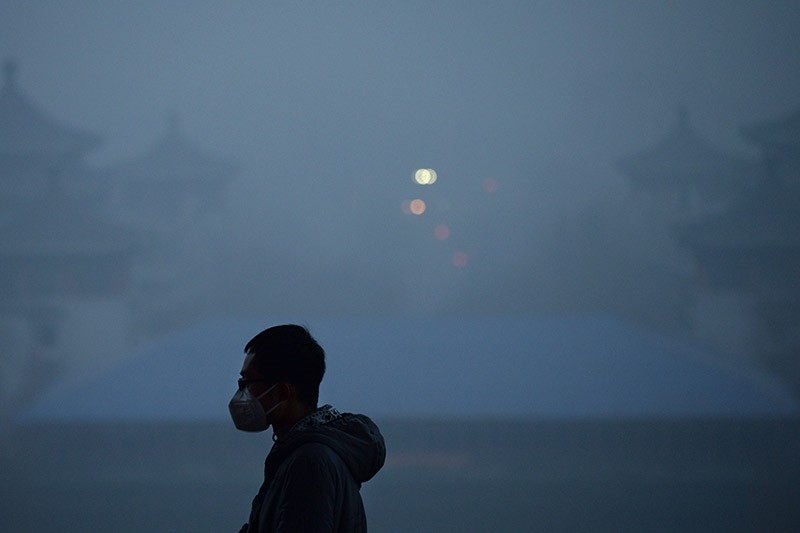 This file photo taken on December 20, 2016 shows a man wearing a mask visiting a park amid heavy air pollution in Beijing. (AFP Photo)