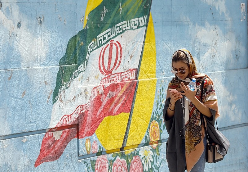An Iranian girl walks next to a wall painting of Iran's national flag while using her cellphone in a street, in Tehran, Iran, April 28, 2018. (EPA Photo)
