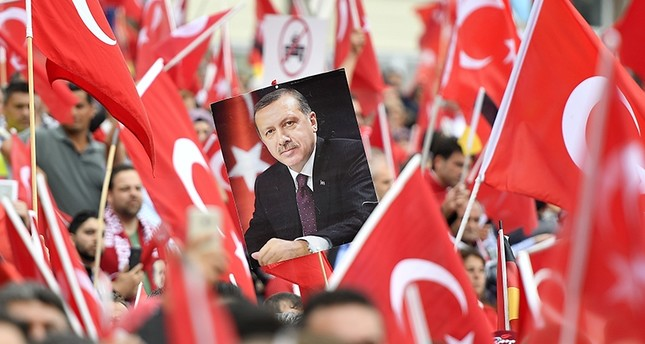 A picture of President Erdoğan is framed by national flags during a demonstration in Cologne, Germany (AP Photo)