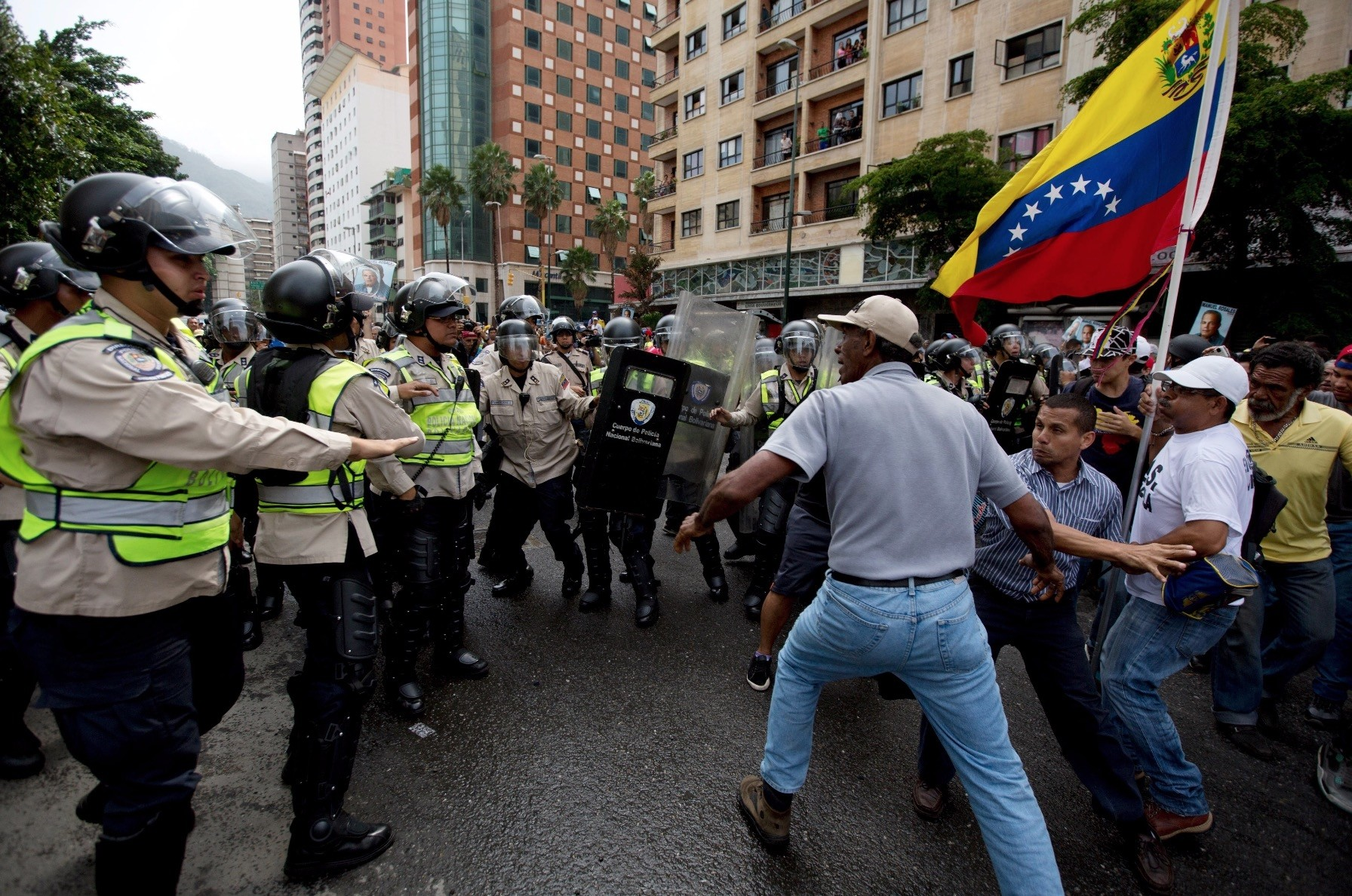 Anti-government demonstrators try to break through a police barrier in an effort to reach the headquarters of the national electoral body in Caracas, May 18, 2019.