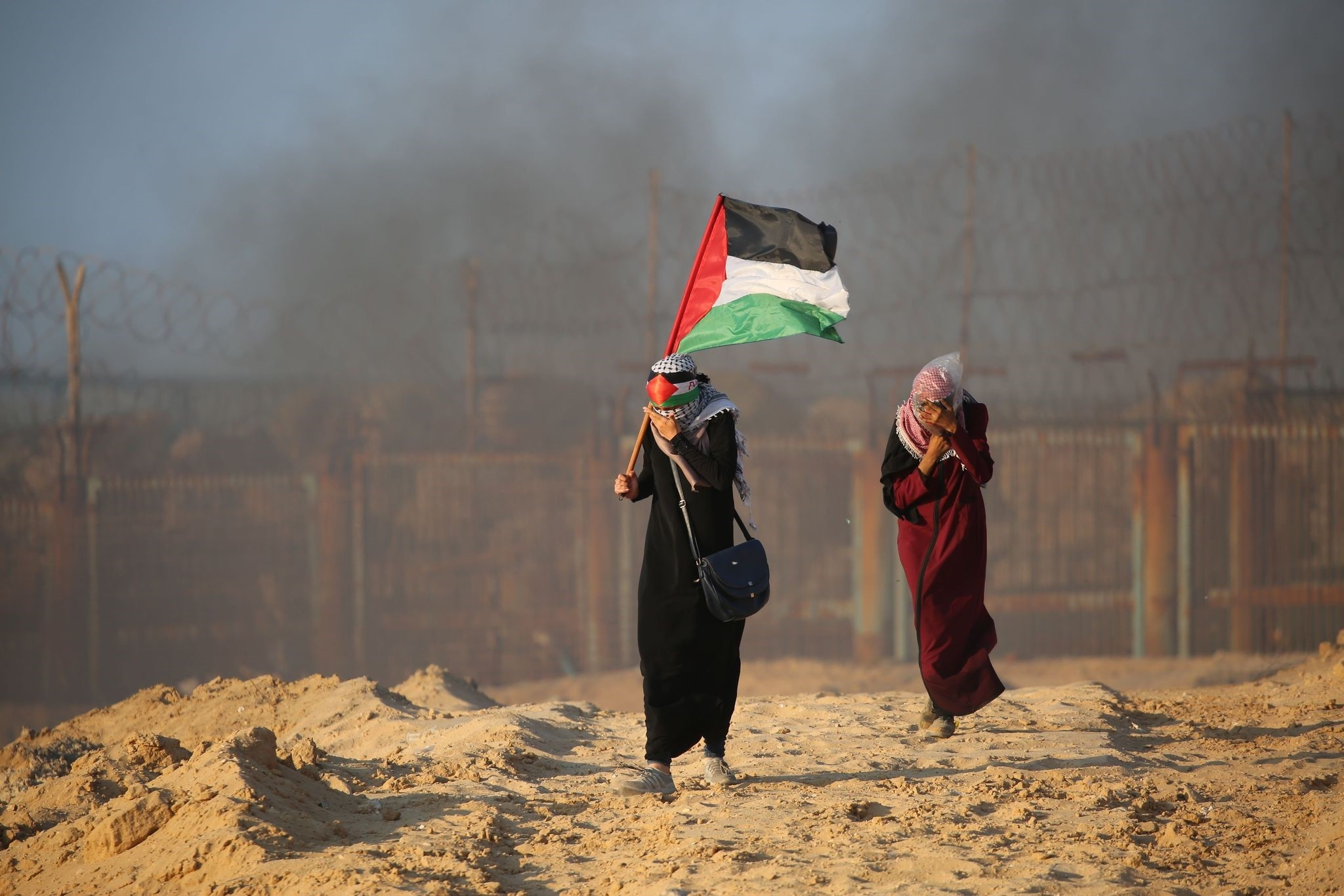 A Palestinian woman carries her national flag on a beach in Beit Lahia near the maritime border with Israel, Sept. 17.
