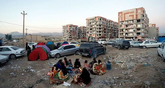 Iranian victims of an earthquake gather outdoors near a fire in the city of Pole-Zahab in Kermanshah Province, Iran, 13 November 2017 EPA Photo