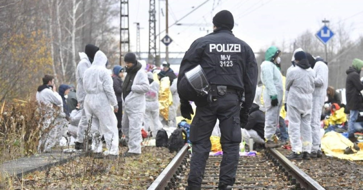 A police officer watches over climate activists from Ende Gelaende as they block train tracks next to the Jaenschwalde power plant in eastern Germany on November 30, 2019. (AFP Photo)