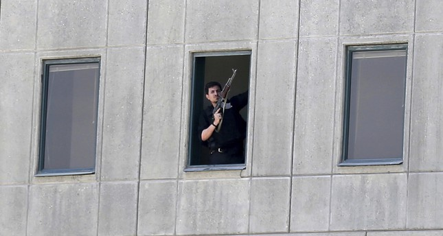Armed man stands in a window of the parliament building during an attack by militants in Tehran, Iran. (Fars News Agency via AP)