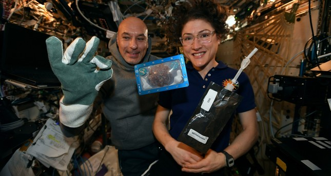 US astronaut Christina Koch and Italian astronaut Luca Parmitano pose for a photo with a cookie baked on the International Space Station Photo from Twitter