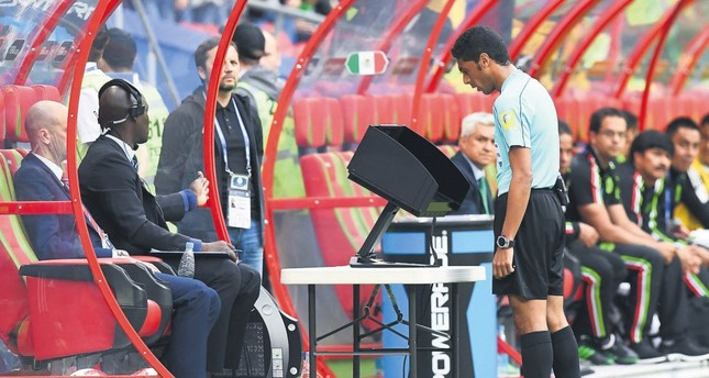 The assistant referee check the video playback during the 2017 Confederations Cup group A football match between Mexico and Russia at the Kazan Arena Stadium.