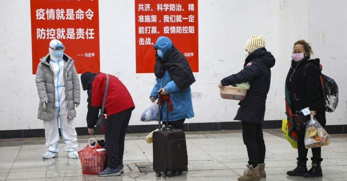 A medical worker in a protective suit looks at patients who diagnosed with the coronaviruses arrive at a temporary hospital which transformed from an exhibition center in Wuhan in central China's Hubei province, Feb. 5, 2020. (AP Photo)
