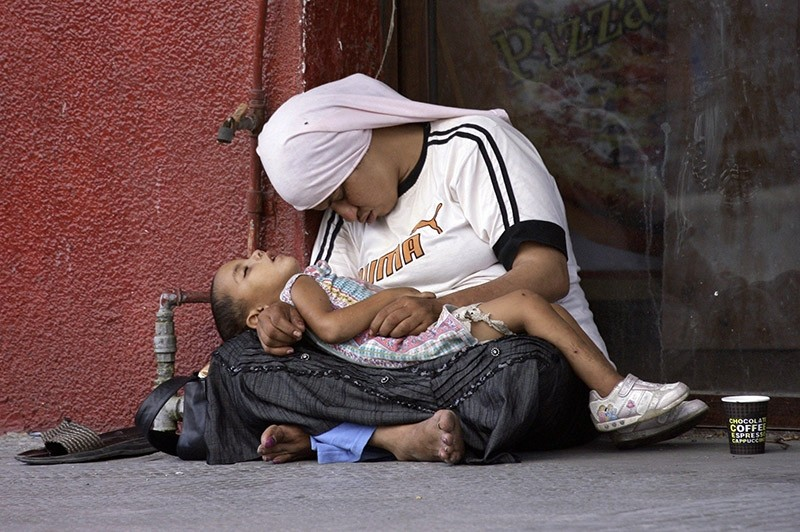 A Syrian refugee woman holds her child as they doze off on the sidewalk of a street in the southern Lebanese city of Sidon on July 18, 2013. (AFP Photo)