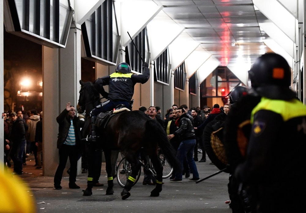 A Dutch mounted police officer raises a truncheon during protests against police treatment of a minister,preventing her from addressing people in front of Turkish Consulate in Rotterdam,which led to a diplomatic crisis between Turkey & Netherlands.