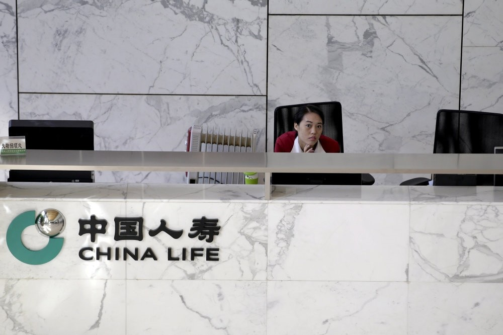 An employee sits at the reception of the headquarters building of China Life insurance in Beijing. China would likely lean on cash-rich SOEs like China Life Insurance to bail out the largest of the struggling companies.