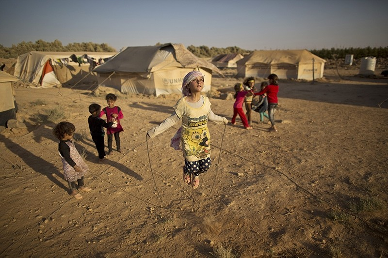 In this July 19, 2015 file photo, Syrian refugee girl, Zubaida Faisal, 10, skips a rope while she and other children play near their tents at an informal tented settlement near the Syrian border on the outskirts of Mafraq, Jordan. (AP Photo)