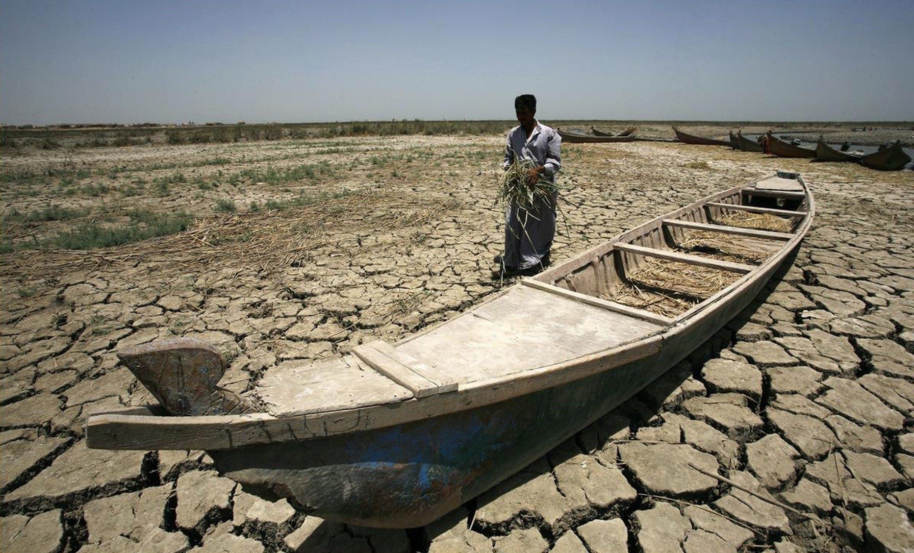 An Iraqi man passes by a boat resting on the dry and cracked ground in the Chibayish marshes, near the Iraqi city of Nasiriyah, in 2015.