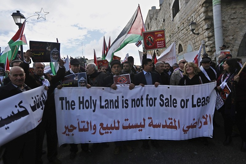 Palestinian demonstrators react during a protest against the visit of Greek Orthodox Patriarch of Jerusalem Theophilos III, during a protest against his visit the Church of the Nativity, in the West Bank city of Bethlehem, Jan. 6, 2018. (AP Photo)