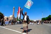 يمني من أنصار جماعة الحوثي يحمل لافتة منددة بإسرائيل الفرنسية