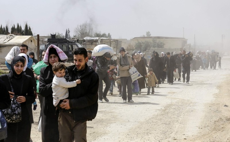 Syrians civilians evacuated from eastern Ghouta pass with belongings through the Assad regime-controlled corridor in Hawsh al-Ashaari, east of the enclave town of Hamouria on the outskirts of the capital Damascus, Syria, March 15, 2018. (AFP Photo)