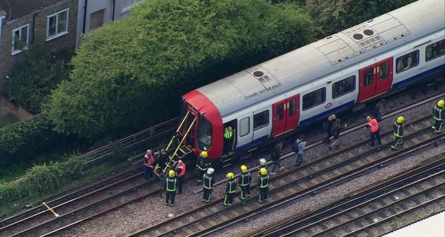 In this aerial image made from video, emergency workers help people to disembark a train near the Parsons Green Underground Station after an explosion in London Sept. 15, 2017. (AP Photo)