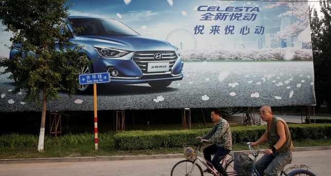 Men cylce past an advertising billboard for Hyundai cars opposite the plant of Hyundai Motor Co in Beijing.