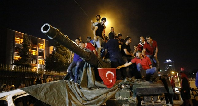 Anti-coup civilians stand on a tank controlled by putschist troops on July 15, 2016 during FETÖ's coup attempt.