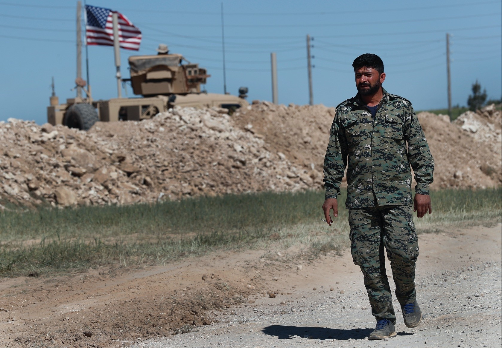 A U.S-backed Syrian Manbij Military Council soldier passes a U.S. position near the tense frontline with Turkish-backed fighters, in Manbij, Syria, April 4.