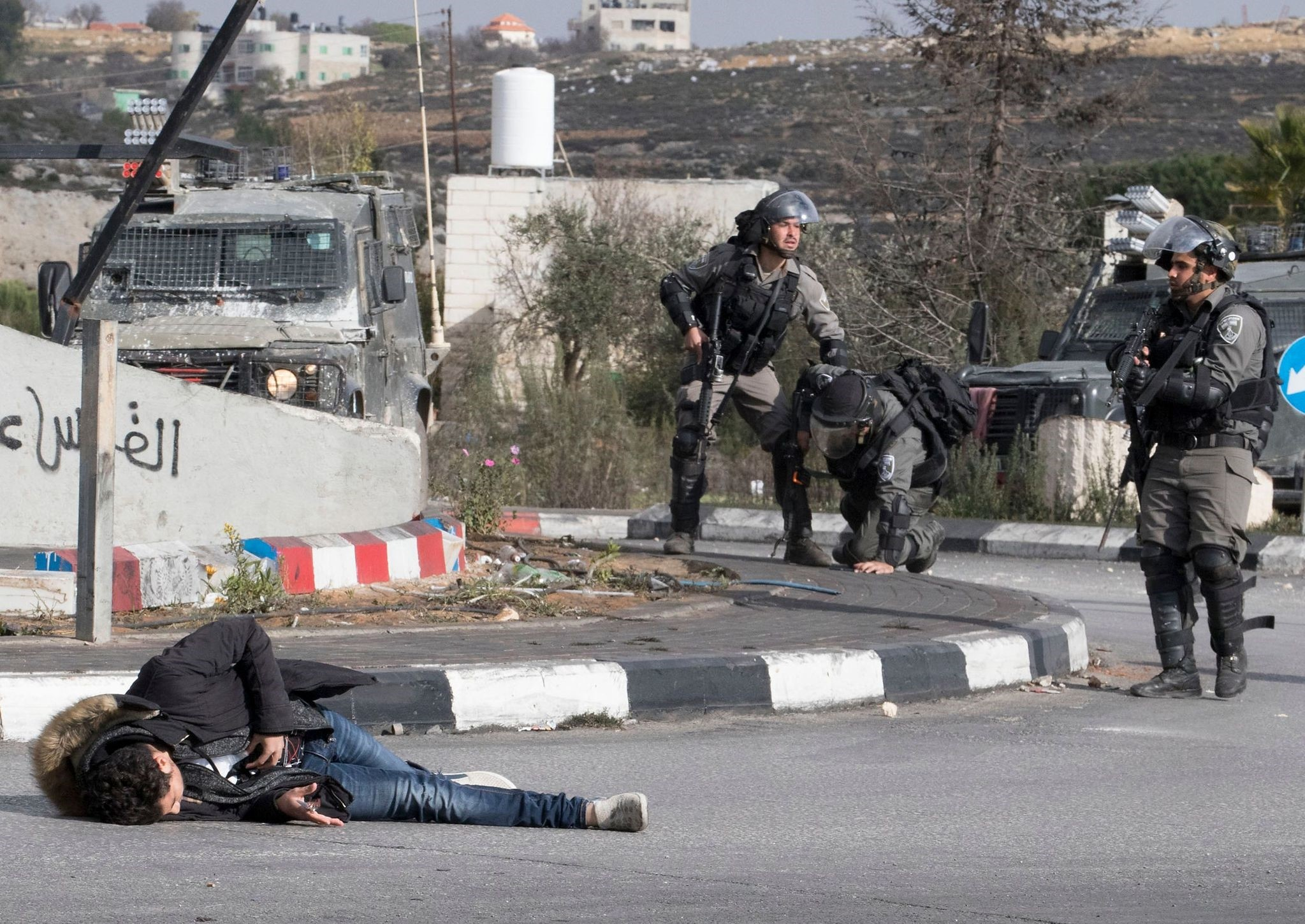A Palestinian man clutches his stomach after he was shot by Israeli soldiers, in reaction to his stabbing attack on a soldier, in the Israeli occupied West Bank town of al-Bireh on December 15, 2017. (AFP Photo)