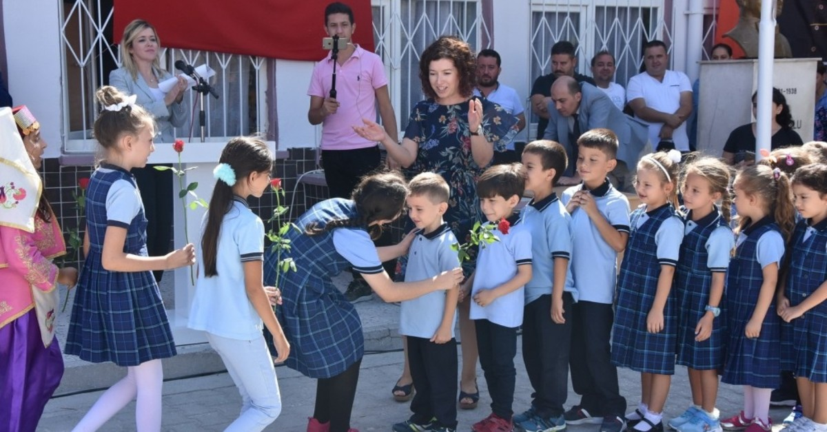 Fourth graders welcome first graders to the school, giving them flowers, on the first day of the school year at a school in Manisa's Akhisar district, Sept. 9, 2019.