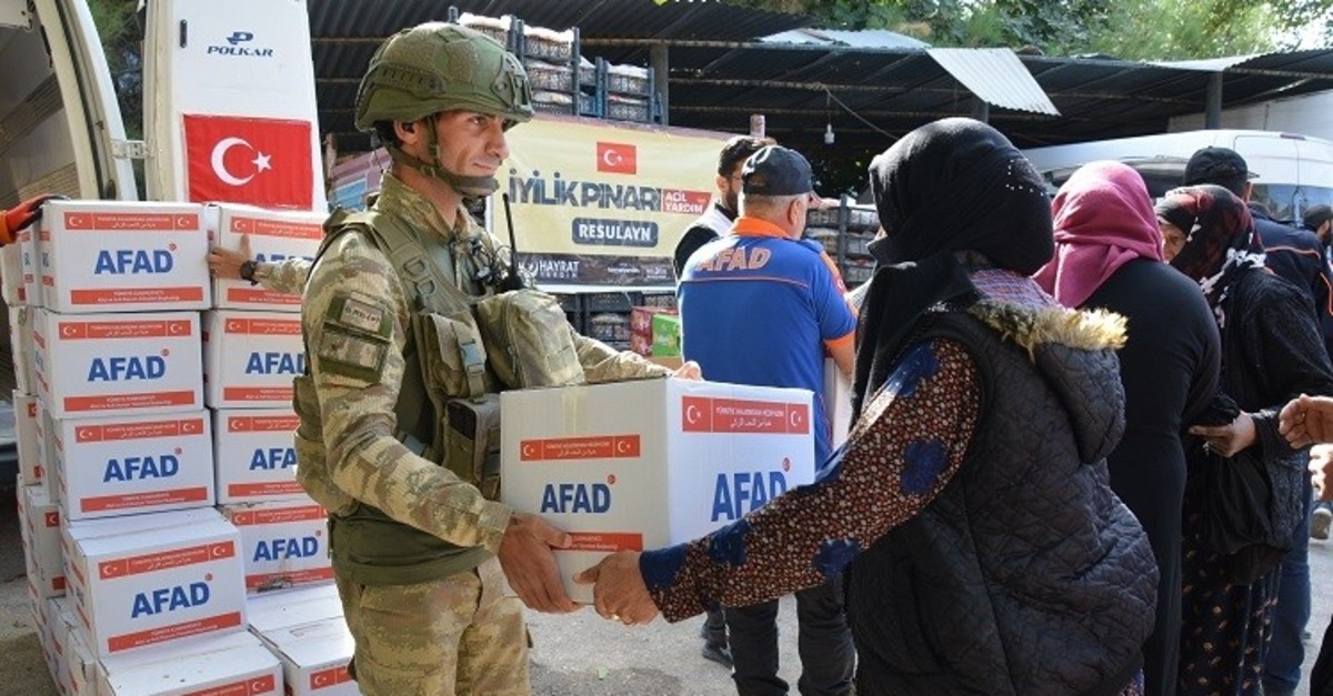 Turkish soldiers distribute humanitarian aid boxes to locals in Syria's Tal Abyad (IHA Photo)
