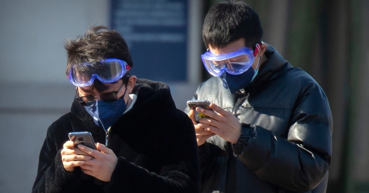 Travelers wear face masks and goggles as they use their smartphones outside the Beijing Railway Station in Beijing, Saturday, Feb. 15, 2020. (AP Photo)