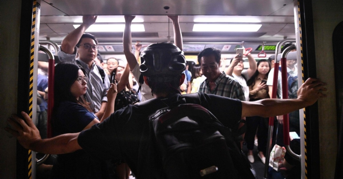 A protester blocks the MTR underground train from closing as protesters blocked the train doors at Fortress Hill station in Hong Kong on August 5, 2019 in their efforts to disrupt the morning rush hour commute. (AFP Photo)