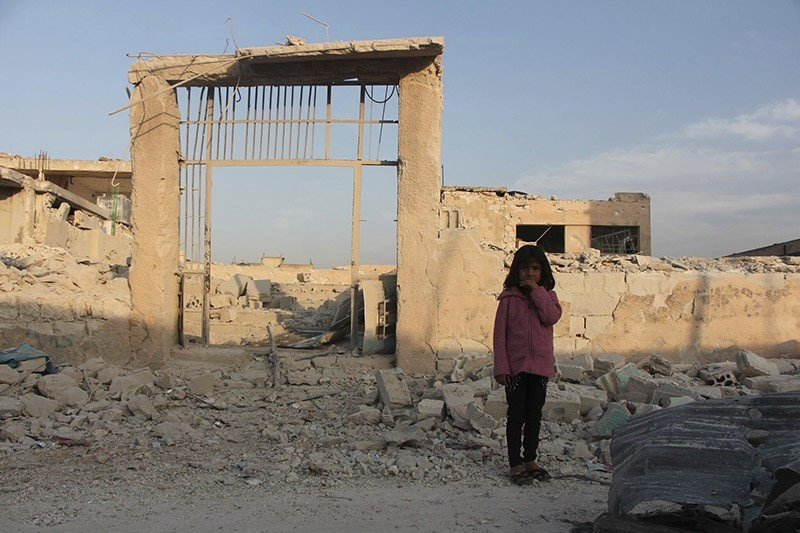 A young girl stands in front of her damaged school, in Idlib, north Syria. (AP File Photo)