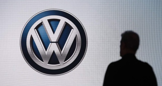 In this Wednesday, Nov. 28, 2018, file photo an attendee waits for the start of a news conference at the Volkswagen booth at the Los Angeles Auto Show in Los Angeles. AP Photo
