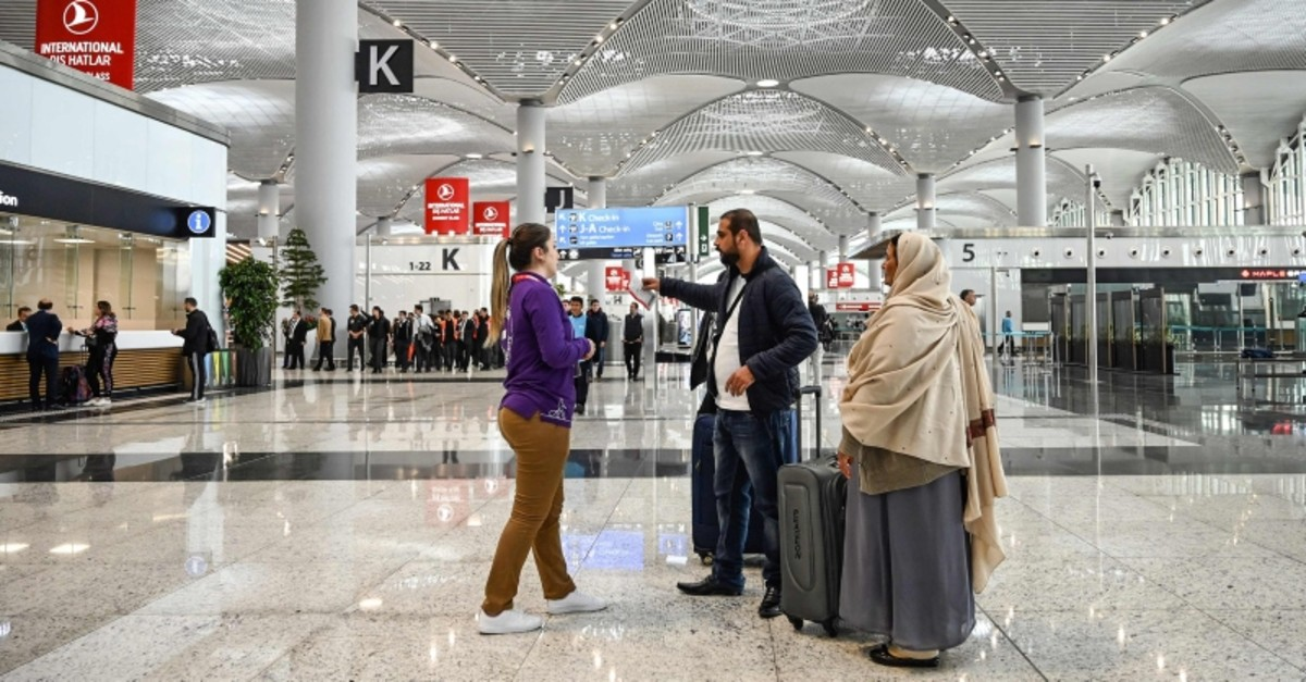 A staff member gives information to passengers in a hall of the new ,Istanbul Airport, on the first day after it moved from Ataturk International airport on April 6, 2019 in Istanbul. (AFP Photo)