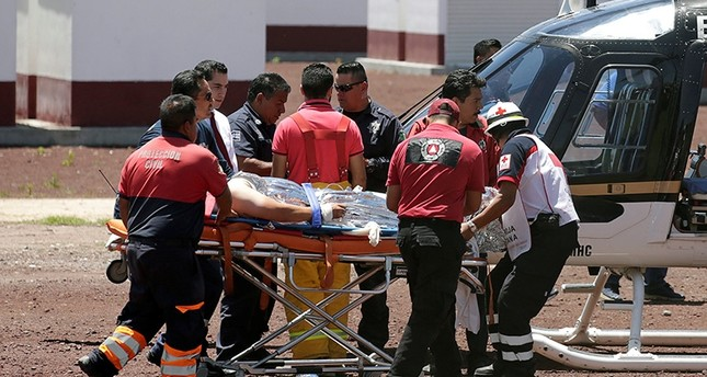 Paramedics wheel a stretcher carrying a man injured due to fireworks explosions toward a helicopter in the municipality of Tultepec, on the outskirts of Mexico City, Mexico on July 5, 2018. (Reuters Photo)