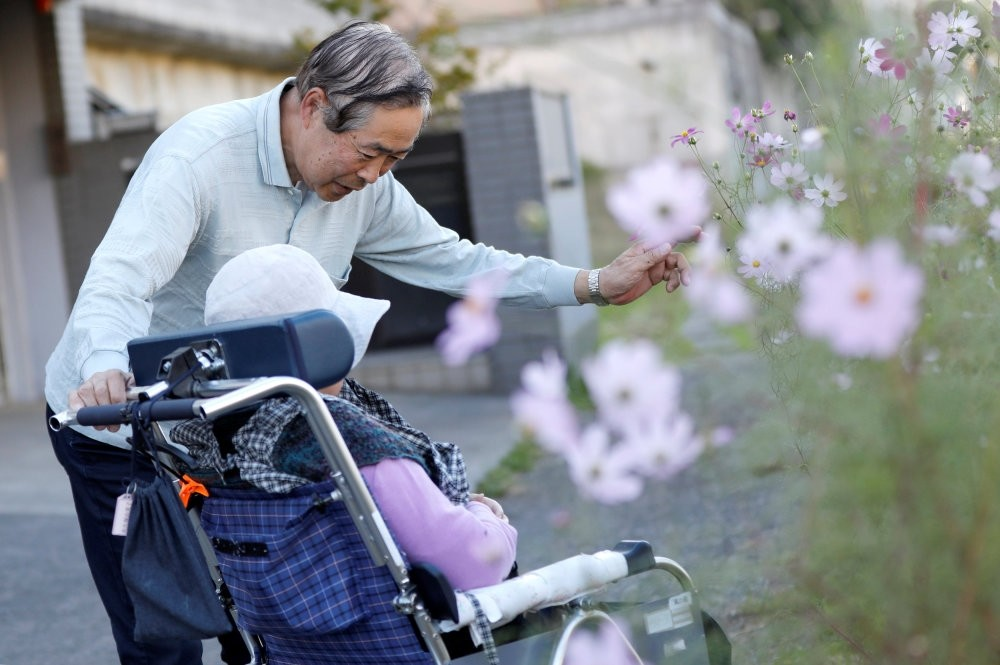 Eiichi Okubo (top), 71, speaks to his wife Yumiko, 68, who suffers from dementia, near her care house in Tokyo, Japan, Oct. 29.