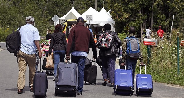 A family from Haiti approach a tent in Saint-Bernard-de-Lacolle, Quebec, stationed by Royal Canadian Mounted Police, as they haul their luggage down Roxham Road in Champlain, N.Y., Monday, Aug. 7, 2017 (AP Photo)