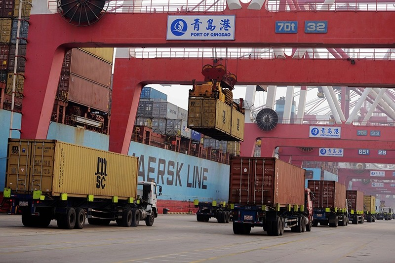 This  April 12, 2016 file photo shows trucks transporting containers at a port in Qingdao, China. (AFP Photo)