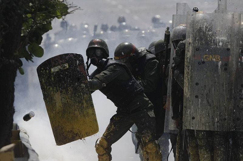 Bolivarian National Guards shield themselves from a jar of fecal matter flying toward them, thrown by anti-government protesters in Caracas, Venezuela, Wednesday, May 10, 2017. (AP Photo)