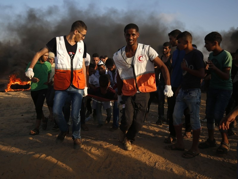 Palestinian protesters and rescuers carry a wounded protester during a demonstration at the Israel-Gaza border, in Khan Yunis in the southern Gaza Strip on August 3, 2018. (AFP Photo)