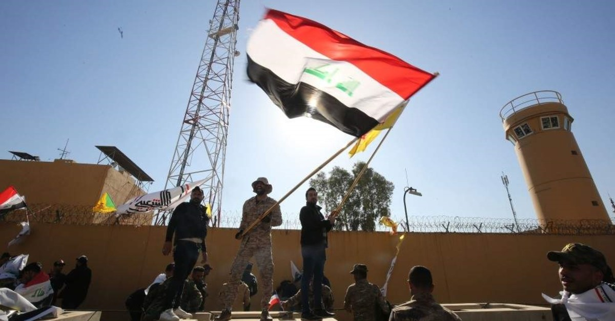 Iraqi protesters wave a national flag in front of the outer wall of the US embassy in Baghdad's Green Zone during an angry demonstration on Dec. 31, 2019 to denounce weekend US air strikes that killed Iran-backed fighters in Iraq. (AFP Photo)