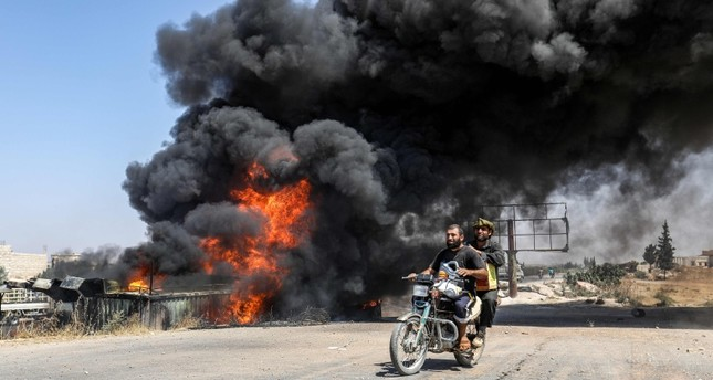 Men ride a motorcycle past a plume of smoke from a blaze at a vehicle gathering point for civilians fleeing from the south of Idlib province, which was hit by reported government forces' bombardment (AFP Photo)
