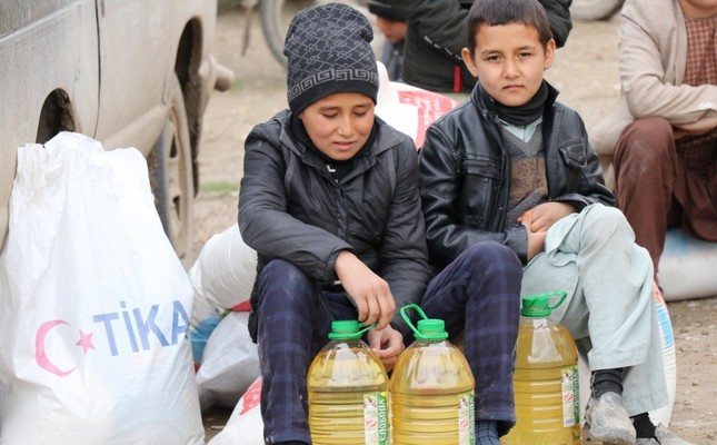 Two children sit beside packages of food aid distributed by TİKA in Kunduz, Feb. 11, 2019.