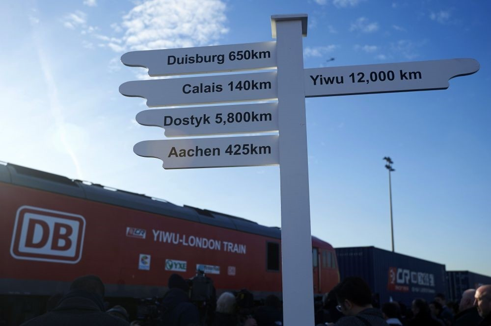 A sign showing the distance in kilometers to various destinations as a freight train transporting containers laden with goods from China, arrives at DB Cargo's London Eurohub rail freight depot in east London.