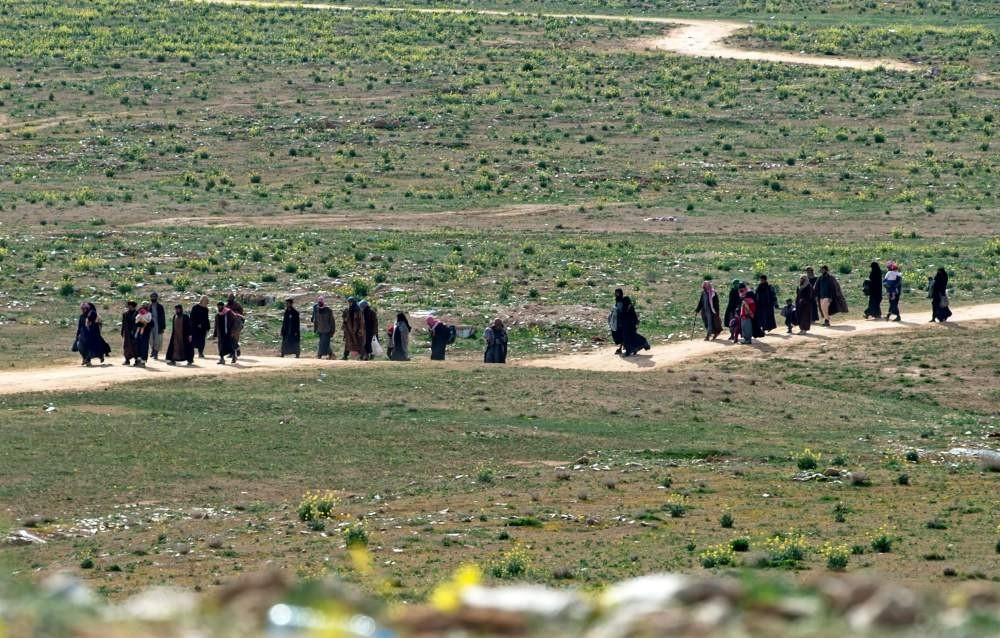 Men believed to be Daesh terrorists and their families walk in a field as they leave the terrorist group's last territory, the village of Baghouz, Feb. 13, 2019.