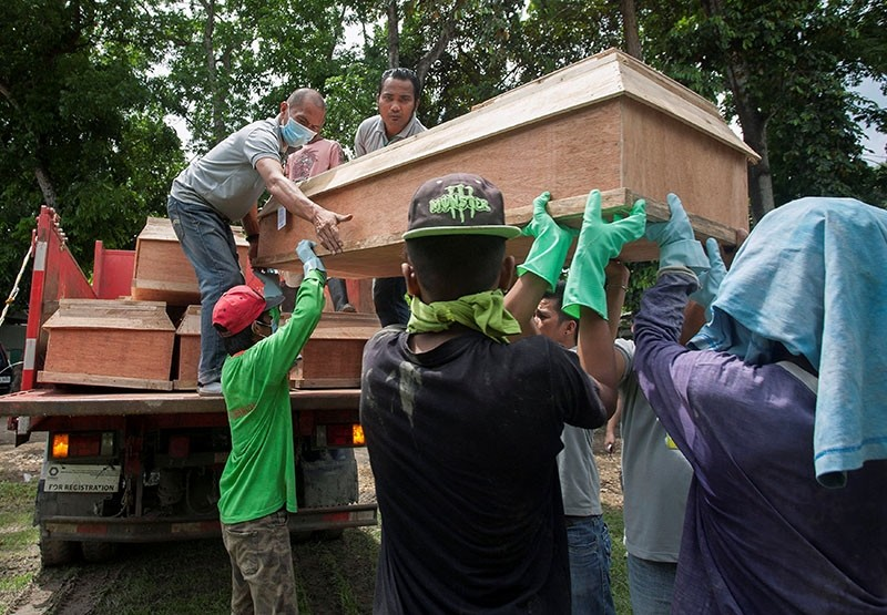 Funeral workers lift a coffin containing one of the civilians who was killed in a firefight between troops and insurgents from the Maute group during a mass burial ceremony at the cemetery in Iligan city, Philippines June 15, 2017. (Reuters Photo)